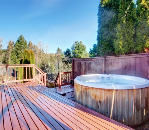Georgous large back patio with red wooden deck, and jacuzzi.